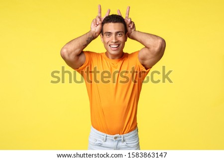 Cute masculine and silly hispanic boyfriend in orange t-shirt, make peace gesture, bunny ears behind Stock photo © benzoix