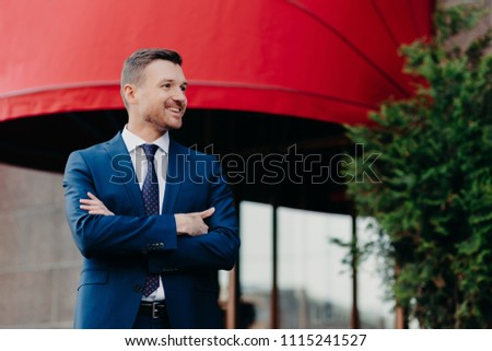 Glad prosperous businessman keeps arm folded, wears formal suit, looks aside with positive expressio Stock photo © vkstudio