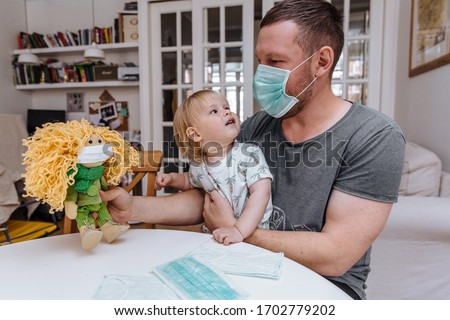 Young child girl at home, wearing a protection mask and gaming on a tablet, Coronavirus quarantine. Stock photo © Illia
