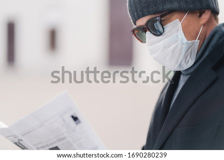 Cropped shot of male model protects against contagious disease or coronavirus, wears hygienic mask t Stock photo © vkstudio