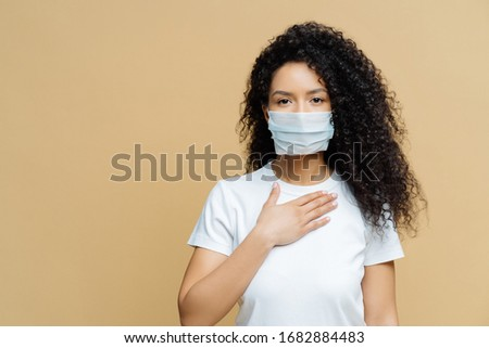 Serious Afro American woman wears medical face mask, has problems with breathing, presses hand to ch Stock photo © vkstudio