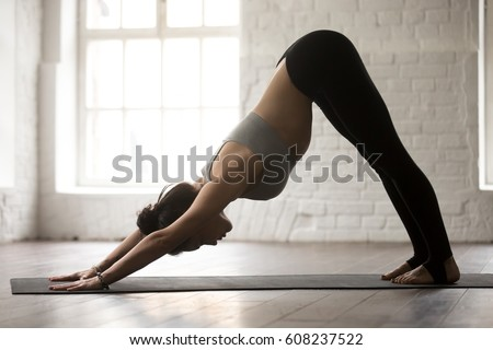 Young sporty woman doing yoga asana downward facing dog under industrial bridge Stock photo © GVS