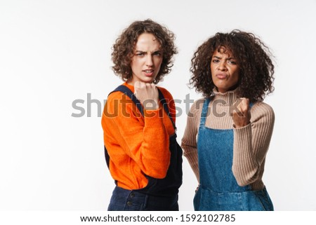 Portrait of angry multinational women showing fists at camera Stock photo © deandrobot