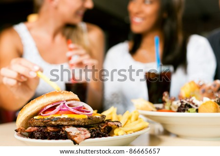 young woman eating hamburger and drinking out of a straw while making a call stock photo © photography33