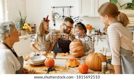 Family gathered around kitchen table preparing pumpkins Stock photo © photography33