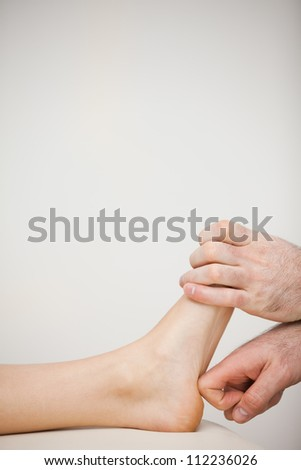 Chiropodist using his index finger to massage a foot in a medical room Stock photo © wavebreak_media
