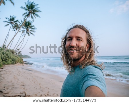 portrait of young happy man sharing his travel photo and video f stock photo © hasloo