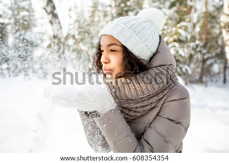 Teenage Girl Wearing Warm Winter Clothes And Hat Blowing Snow In Stock photo © monkey_business