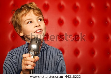 Portrait of boy with microphone on rack against red wall looking aside. Horizontal format. Stock photo © Paha_L
