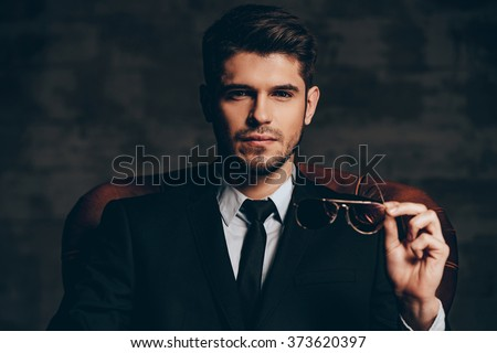 portrait of young man closing his jacket while posing in dark s Stock photo © feedough