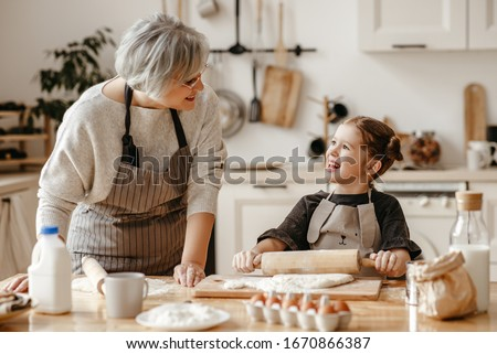 Grandmother and granddaughter looking at each other while holding dough and rolling pin Stock photo © wavebreak_media