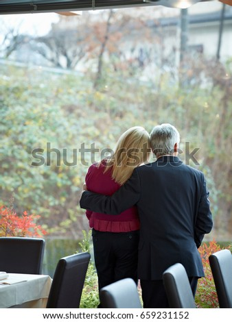 senior couple having an intimate moment in a restaurant whilst looking out a window stock photo © is2