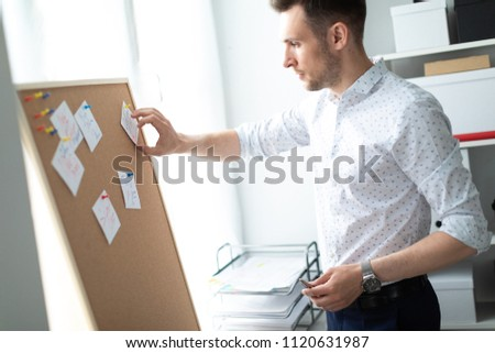 A young man stands near a board with stickers and holds a pen in his hand. A young man tears off a s Stock photo © Traimak