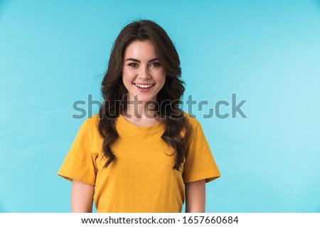 Jovem mulher bonita posando isolado amarelo Foto stock © deandrobot