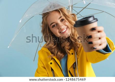 photo of joyful woman 20s wearing yellow raincoat standing under stock photo © deandrobot