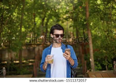 Photo of smiling man 30s wearing sunglasses, drinking takeaway c Stock photo © deandrobot