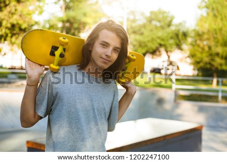 Photo of brunette skater guy 16-18 in casual wear standing with  Stock photo © deandrobot