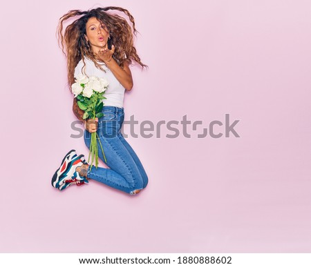 Girl's hands with tattoo hold a bouquet of fresh roses in a color of the year 2019 Living Coral Pant Stock photo © artjazz