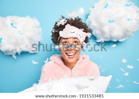 Pretty young girl wearing pajamas holding a feather Stock photo © deandrobot