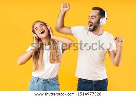 Portrait of joyful couple man and woman, wearing earphones sitti Stock photo © deandrobot