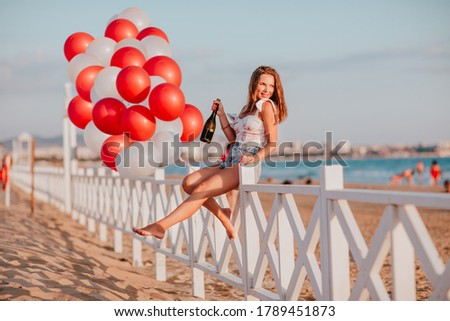 Young woman in jeans shorts posing against the blue sea. Wearing jeans stylish shorts and striped sh stock photo © galitskaya