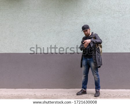 Portrait of good-looking bearded man 30s wearing cap and white t Stock photo © deandrobot