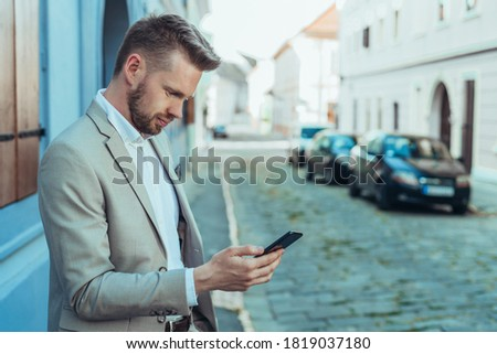 Photo of young businesslike men in suits using smartphones, whil Stock photo © deandrobot