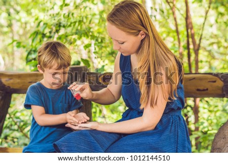 Mother and son using wash hand sanitizer gel in the park before a snack Stock photo © galitskaya