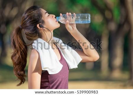 Vonzó sportos nő ivóvíz üveg jogging Stock fotó © galitskaya