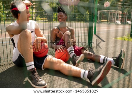 Two intercultural guys in activewear having rest on basketball court Stock photo © pressmaster