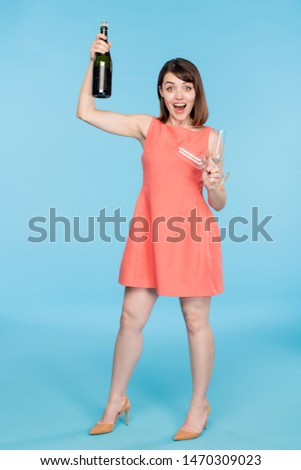 Young pin-up female in red dress holding two flutes and bottle of champagne Stock photo © pressmaster