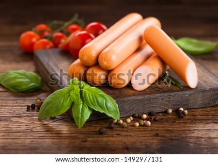 Classic boiled meat pork sausages on chopping board with pepper and basil and cherry tomatoes on lig Stock photo © DenisMArt