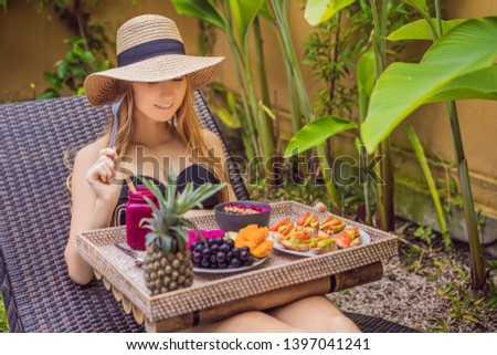 Young woman eating breakfast in a lounge chair on a tray with fruit, buns, avocado sandwiches, smoot Stock photo © galitskaya