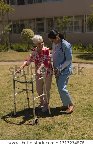 Front view of young happy female doctor helping disabled senior woman in garden on sunny day Stock photo © wavebreak_media