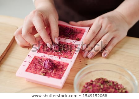 Hands of young woman putting small rosebuds on top of pink soap bars Stock photo © pressmaster