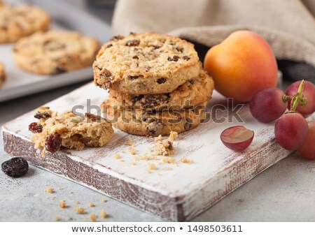 Stock photo: Homemade organic oatmeal cookies with raisins and apricots and bottle of milk on light background.