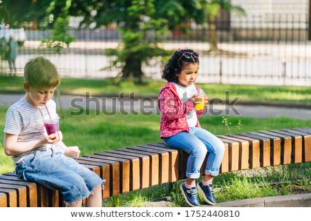 Boy and girl relatives sitting in the Park on a white bench Stock photo © ElenaBatkova
