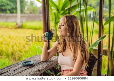 Woman with a cup of tea on the cafe veranda near the rice terraces on Bali, Indonesia Stock photo © galitskaya