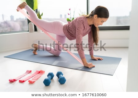 Resistance band fitness at home Asian woman doing leg workout donkey kick floor exercises with strap Stock photo © Maridav