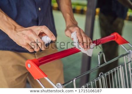 Man hand disinfecting shopping cart with alcohol spray for corona virus or Covid-19 protection Stock photo © galitskaya