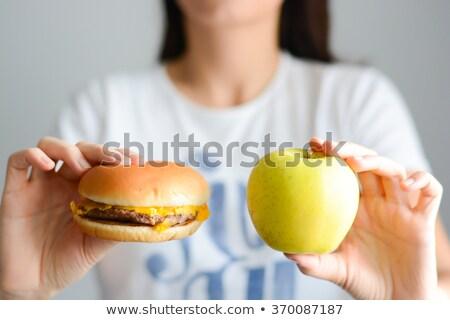 woman choosing between burger and apple stock photo © dolgachov
