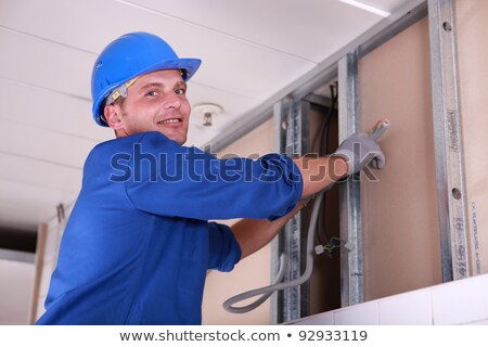 Electrician feeding cable up behind a false wall Stock photo © photography33