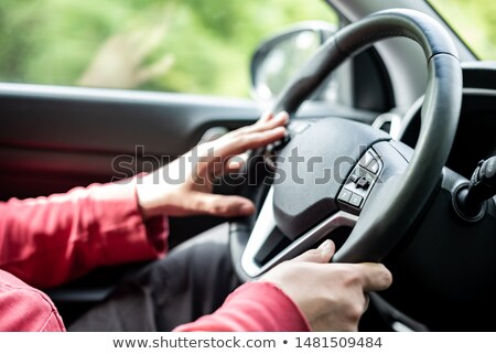driver holds wheel in car stock photo © microolga