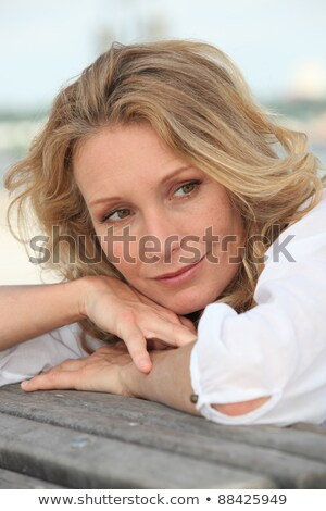 Thoughtful woman resting her head on the back of a bench Stock photo © photography33