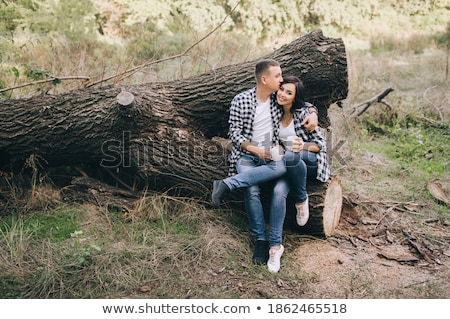 casual man sits in grass with a hand in his hair stock photo © feedough