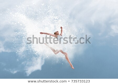 young beautiful dancer jumping into blue powder cloud stock photo © geribody