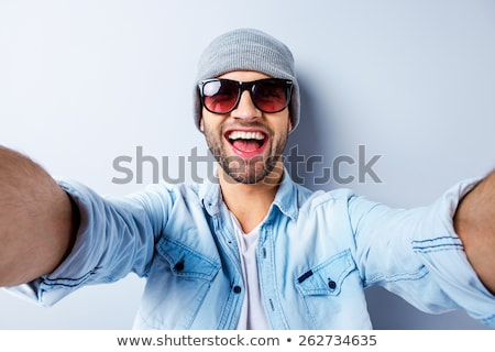 relaxed young man with hat and sunglasses stock photo © feedough