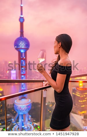 Asian girl drinking cocktail in fancy nightclub or bar Stock photo © Kzenon