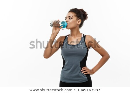 Young sport woman drinking water isolated on white background Stock photo © deandrobot