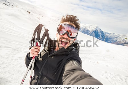 skier taking photo with phone on beautiful winter landscape stock photo © kasjato